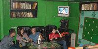 Интерьер клуба Грибоедов в Питере. Книги, телевизор, баян, ковры на стенах.