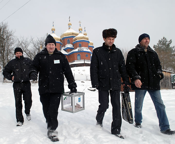 Members of a local election commission walk in front of the church as they bring a ballot box to a voter&quot;s house during the presidential election in the village of Kozova, about 140 km (87 miles) south from the city of Lviv, February 7, 2010. phot.: Vitaliy Hrabar