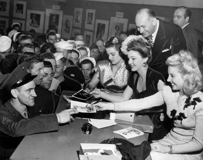 The USO in WWII Jane-Russell_-Toni-Seven-and-Martha-Tilton-sign-pin-ups-for-servicemen-at-the-hollywood-canteen-1944