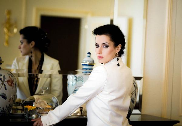 Тина Канделаки в белом пиджаке стоит у зеркала