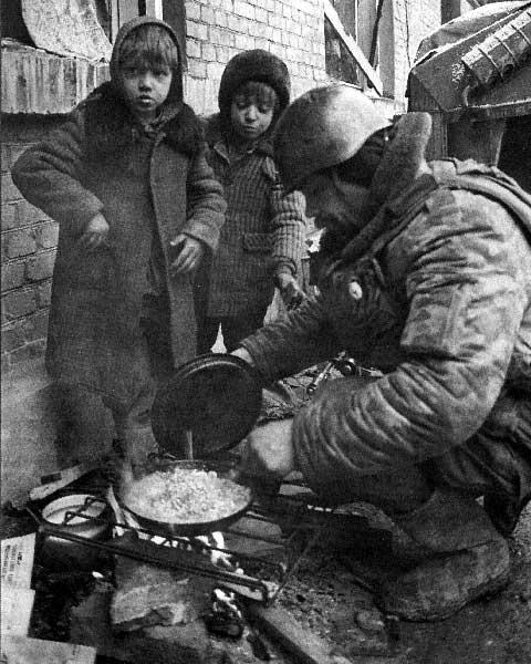 Старший прапорщик Владимир Богорад на самодельном мангале готовит нехитрую снедь – гречневую кашу с тушёнкой
