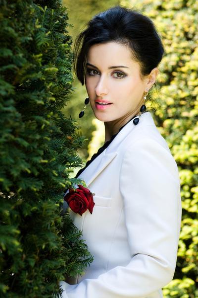 Тина Канделаки в белом пиджаке с красной розой