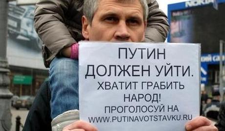 Демонстрант держит плакат ПУТИН ДОЛЖЕН УЙТИ во время запрещенного властями митинга в ДЕНЬ ГНЕВА 20 марта на Пушкинской площади в Москве